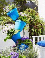 Blue flower pots placed crookedly on a broom handle on a balcony to save space