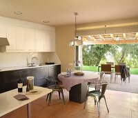 Retro metal chairs at round table in open-plan kitchen adjoining terrace with view into garden