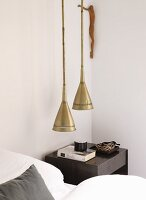 Pendant lamps with brass lampshades and bedside table next to bed