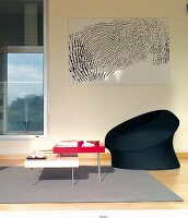 Colourful set of coffee tables and black easy chair on grey rug below black and white artwork on wall