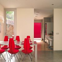 Dining table and red, upholstered, designer chairs on polished concrete floor; view through open doorway into kitchen with bar stools at counter