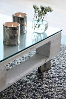 Ceramic tealight holders shaped like tin cans on coffee table made from white-painted wooden pallet, glass top and castors
