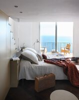 Double bed against fitted staircase and balcony with sea view in background