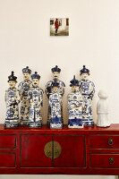 Blue and white painted Chinese china figurines on bureau made of red wood