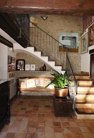 Tiled foyer with bench next to staircase in traditional, Spanish stone house