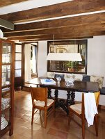 Traditional Spanish table and wooden chairs in dining room with wood-beamed ceiling