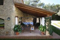 Dining area on roofed terrace of Spanish stone house