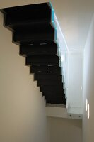 Bottom view of black staircase in narrow, white stairwell