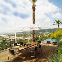 Dining set and parasol on wooden deck with view of town on hillside; infinity pool in background