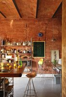 Bar stool with copper seat at breakfast counter in loft-apartment kitchen; open-fronted metal shelving and blackboard on brick wall