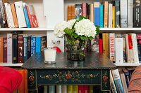 Vase of hydrangeas on side table with floral, country-style painting in front of fitted bookcases