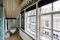 Gable-end windows in attic bathroom with view of houses on opposite street side; screened toilet mounted on knee wall