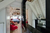 White-painted roof structure and dark installations in attic bathroom with view into bedroom