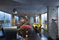 Metal counter, bar stools and yellow sofa on black stone floor below chrome lights suspended from exposed concrete ceiling in open-plan, modern interior
