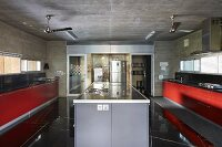 Island counter between kitchen counters with red fronts; stainless steel fridge in background