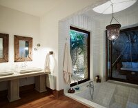 Twin washstand with stone counter and columns and sunken bathtub with steps