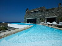 Long, curved pool outside modern, Greek stone house with sun terrace and sea view