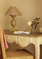 Rattan chair at delicate, carved console table with vintage table lamp with old rose lampshade