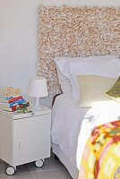 Bed against wall-hanging headboard on partition wall next to small, white table lamp on bedside cabinet on castors