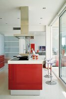 Kitchen island with red fronts and designer bar stools with plexiglas seats in front of sliding glass wall