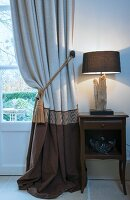 Curtain in shades of brown next to lamp on bedside table
