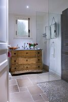 Country-house chest of drawers and pebble-tiles shower with glass partition in bathroom seen through open door