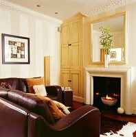 Elegant leather couch in front of fire bowl in open fireplace in traditional, English country house