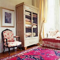 Antique linen cupboard with wire mesh doors next to armchair with butterfly-patterned upholstery