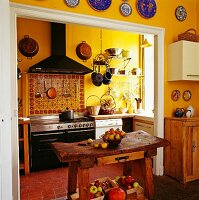 Rustic table in yellow., country-house kitchen with terracotta floor and ceramic splashback