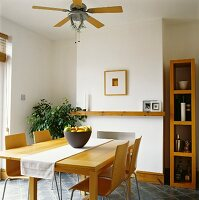 Pale dining table and chairs in modern dining room with ceiling fan
