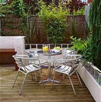 Bistro table and metal chairs on wooden terrace amongst lush garden plants