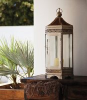 Metal, Oriental-style lantern on wooden chest of drawers
