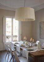 Classic pendant lamp with fabric lampshade above white place settings on wooden dining table with classic chairs