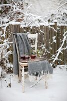 Tray of mulled wine and blanket on old wooden chair in snowy garden