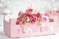 Bouquet of roses in fruit crate painted pastel pink and labelled with decorative lettering spelling 'FLOWERS'