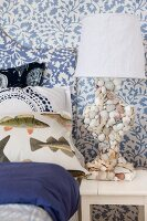 Maritime bedroom with fish-patterned bed linen and lamp base covered in seashells