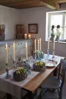 Candlesticks and wreaths on rustic wooden table with runner