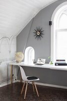 Classic chair with white shell seat at desk below window in grey-painted wall of attic room with arched ceiling