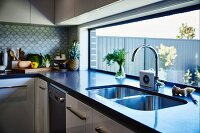 Twin sink in dark counter below long ribbon window in modern fitted kitchen