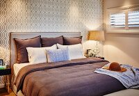 Double bed with brown bedspread, scatter cushions and upholstered headboard against beige, retro wallpaper