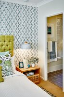 Illuminated bedside table below pendant lamp against retro patterned wallpaper; door leading to ensuite bathroom to one side