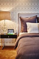 Pillows on double bed with upholstered headboard against wallpaper with beige retro pattern