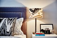 Table lamp on bedside table, bed with scatter cushions and headboard upholstered in blue leather