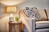 Table lamp on cylindrical, hand-crafted side table next to beige sofa with scatter cushion