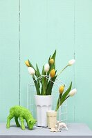 Easter arrangement in pastel shades; tulips in beakers and lamb ornament