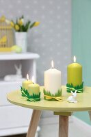 Easter arrangement in shades of green; candles trimmed with felt grass and rabbit ornament on small, round table