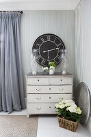 Elegant silver candlesticks in candle lanterns on top of vintage chest of drawers against striped wallpaper and black, vintage-style wall clock in country-house interior