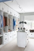 Feminine dressing room with open-fronted white wardrobes
