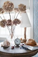 Vintage alarm clock, dried hydrangea flowers and table lamp on side table
