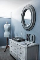 Wooden tray of glass carafes on vintage chest of drawers, tailors' dummy and oval mirror on blue wall